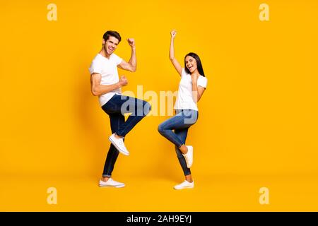 Full body photo of pair lady and guy fans supporting favorite football, team raising fists wear casual outfit isolated yellow color background - Stock Photo
