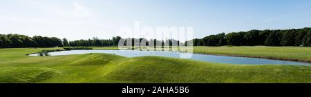panoramic shot of pond in green park against blue sky - Stock Photo