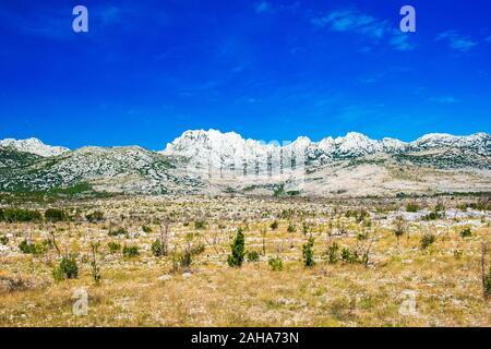 Dalmatian inland landscape and Velebit mountain in background in Croatia - Stock Photo