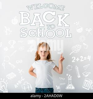 cute redhead kid looking at camera and pointing with finger near welcome back to school letters on white