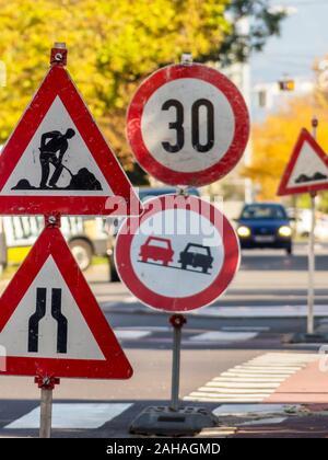 Eine Strsenbaustelle wird durch mehrere Verkehrszeichen abgesichert. - Stock Photo
