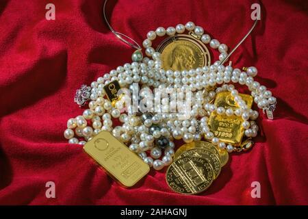 Gold in Münzen und Barren mit Schmuck auf rotem Samt. Symbolfoto für Reichtum, Luxus, Reichensteuer. - Stock Photo