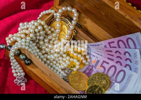 Gold in Münzen und Barren mit Schmuck auf rotem Samt. Symbolfoto für Reichtum, Luxus, Reichensteuer, 500 Euro Scheine, - Stock Photo