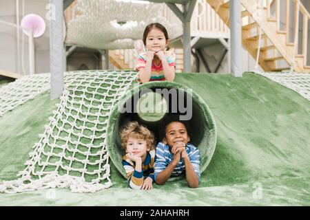 Friendly intercultural little kids having rest on play area at leisure center - Stock Photo