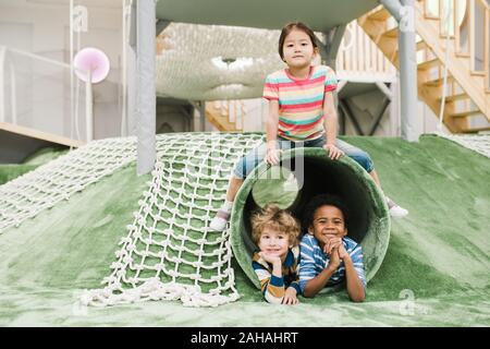 Cheerful and friendly intercultural little kids having fun together on play area