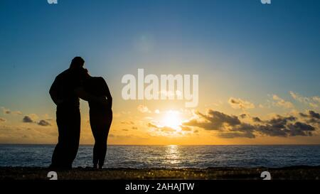 View of a full body of a couple silhouette walking together on the beach at sunset in summer. - Stock Photo