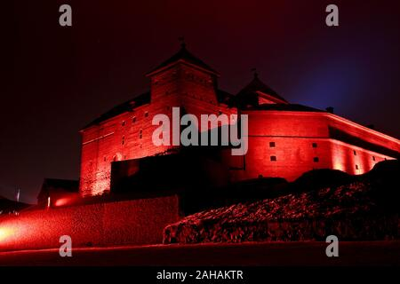 A medieval Häme Castle in bright red and artistic lightning - Stock Photo