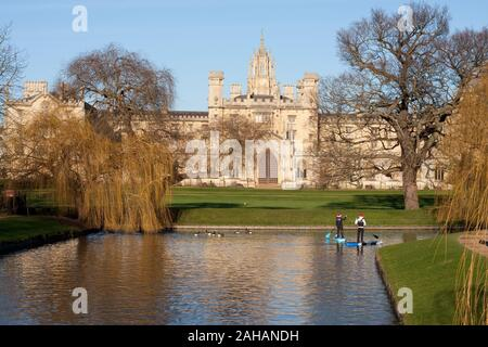 Two people on stand up paddle boards on the River Cam in Cambridge, in front of New Court, part of St John's College - Stock Photo