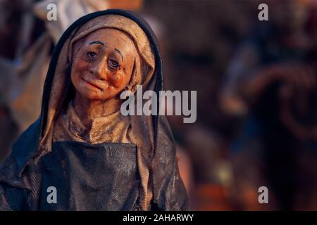 Christmas nativity scene represented with statuettes. Close-up of statuette of a woman at work. - Stock Photo