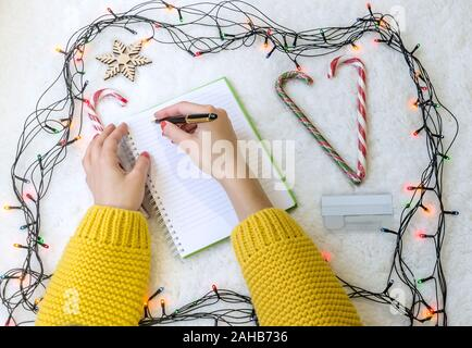 female hands over a notepad, a ballpoint pen and a telephone on the background of the New Year's Eve, close up - Stock Photo