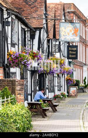 Amersham, England - August 22nd 2019: A man sits outside the Kings Arms Hotel in the old town. The hotel dates from the 15th century. - Stock Photo