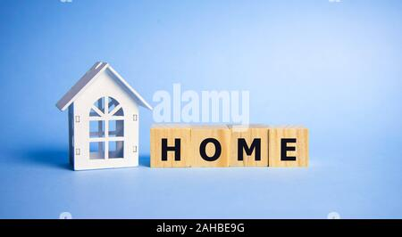 Stock word home spelled on alphabet wooden block letters on old weathered wood blocks over blue, home concept. - Stock Photo