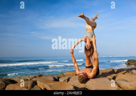 Fit young couple doing acro yoga at spa retreat on sea beach. Active woman on partner feet, balancing at handstand acroyoga pose. Healthy lifestyle. - Stock Photo