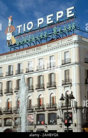 The landmark Tio Pepe sign above Puerta del Sol Square with the statue of Carlos III Charles III of Spain in Madrid. - Stock Photo