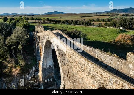 VULCI, ITALY - DECEMBER 26, 2019: The Badia bridge and castle, medieval dating back to the 13th century, an ancient Etruscan city in the territory of - Stock Photo