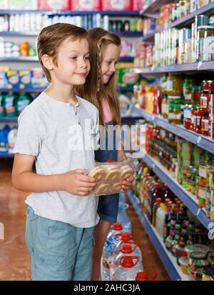 Happy  kids looking preserved meal in grocery shop, family in supermarket - Stock Photo