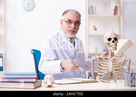 The aged male doctor with skeleton - Stock Photo