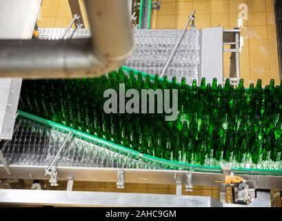 View of empty bottles on conveyor of bottling line at modern brewery - Stock Photo