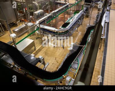 Empty beer bottles on conveyor belt of modern bottling line at brewery - Stock Photo