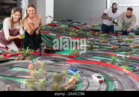 Gambling adult men and women play in childrens racing track - Stock Photo