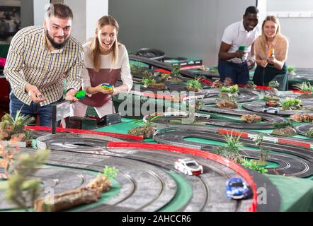 Gambling adult men and women play emotionally in childrens racing track - Stock Photo