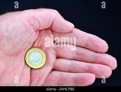 A British one pound coin in the palm of a man's hand against a dark background - Stock Photo