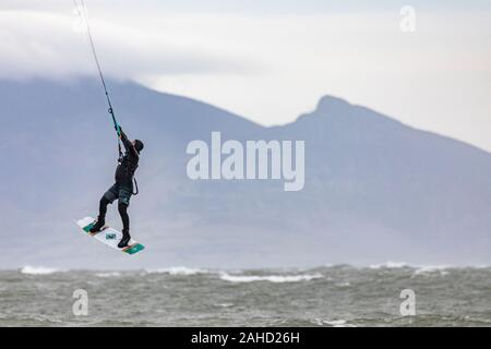 Anglesey, North Wales, 28tht December 2019. UK Weather:  Mild and windy weather at Newborough Beach on the west coast of Anglesey, with speed restrictions on bridges crossing to the island.  Flintshire, Wales. A kite boarder making use of the windy conditions at Newborough Beach with a backdrop of the coastal mountains on the mainland in the distance, Anglesey, Wales © DGDImages/AlamyLiveNews - Stock Photo