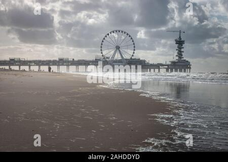 Scheveningen, the Netherlands - October 3, 2017: Low angle view of pier of Scheveningen with ferris wheel and bungee tower, the Netherlands - Stock Photo