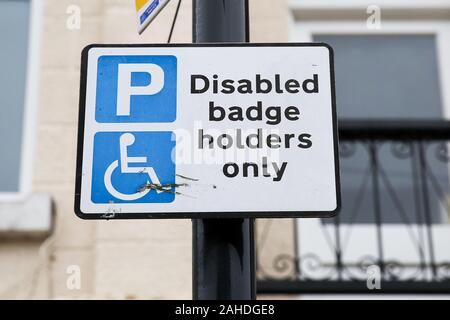 A disabled badge holder only sign is seen in north London.Thousands of people with hidden disabilities have been given blue badge parking permits since new rules were introduced. - Stock Photo