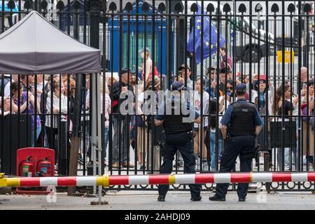 Tourists and visitors, watched by armed police at the gates to Downing Street in Westminster, London, UK - Stock Photo