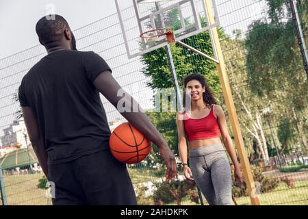 Young african descent couple standing on basketball court outdoors man back view holding ball looking at woman walking towards smiling cheerful - Stock Photo