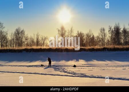 Silhouette of a lone fisherman on a snow-covered river, in the light of the rising sun - Stock Photo