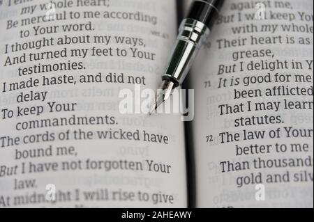 Open Bible in close-up at Psalm 119 with a fountain pen. Horizontal shot. - Stock Photo