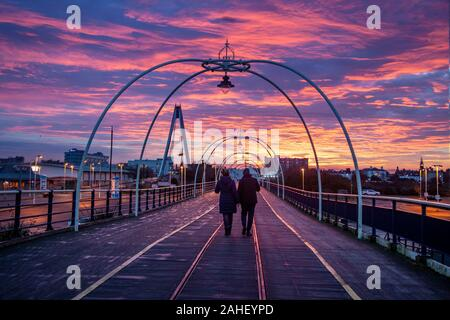 Southport, Merseyside, UK. 29th December, 2019.  Rayleigh scattering;  The sky turned blood red this morning as the sun rose over Merseyside. People walking on the pier enjoy Intense fiery winter red and orange skies at dawn as sun rises in Southport, Red sky in the morning, shepherd's warning' first appears in the Bible in the book of Matthew. It is an old weather saying often used at sunrise to signify the changing sky and was originally known to help  prepare for the next day's weather.  Credit: MediaWorldImages/AlamyLiveNews. - Stock Photo
