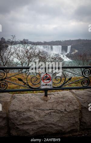 Niagara Falls, Ontario, Canada, December 27 2019: Sign stating danger of falling down at Niagara Falls with American Falls in background - Stock Photo