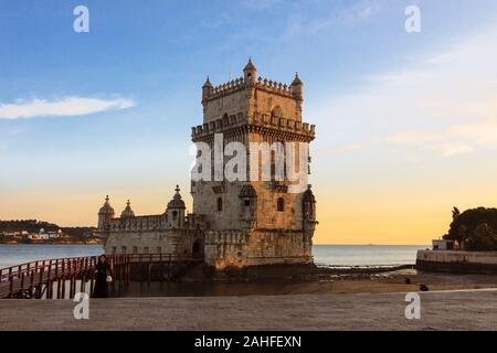 Lisbon, Portugal : A woman stands next to the Belém Tower at sunset. The Unesco listed building was designed in 1515 by Francisco de Arruda  to defend - Stock Photo