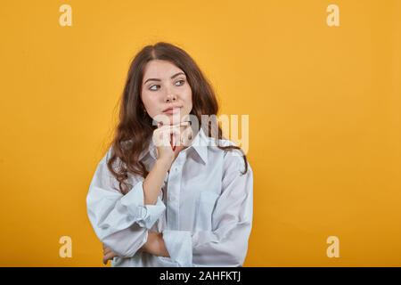 Focused young woman keeping hands on chin, looking aside, having nice haircut - Stock Photo