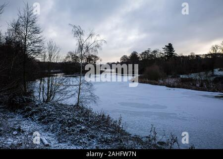 An icy lake with a dusting of snow, leaden grey sky and bare trees during winter in West Yorkshire, U.K. - Stock Photo