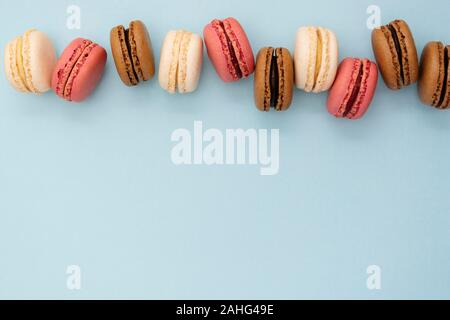 Macarons cakes. Fashion or feminine background delicious macaroons in row on blue background. Social media walpaper. Copy space for text. - Stock Photo