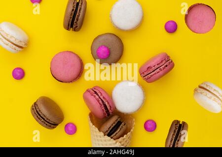 Macarons cakes. Stil life photo of waffle cone with macaroons on yellow background. Flat lay, dessert food. - Stock Photo