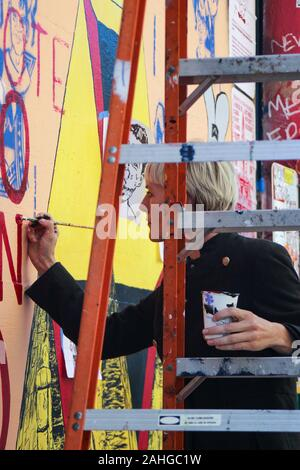Mural artist at work on Clarion Alley in Mission District of San Francisco, United States of America - Stock Photo
