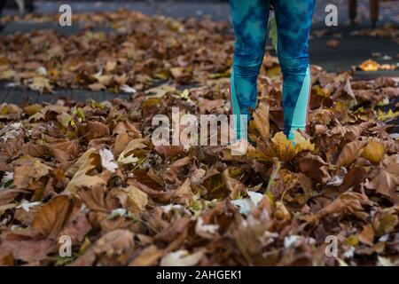 Brown leaves on ground covering feet of little girl in fall season. Child in green leggings standing outdoors on autumn day
