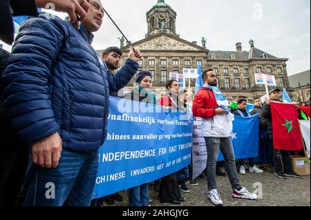 The Dam, Amsterdam, The Netherlands. Sunday 29th December, 2019. An Anti-Chinese demonstration this afternoon, as a large group of protesters gathered to denounce the systematic policy of China, to erase the ethnic and cultural identity of Uighurs and other Muslim minorities in Xinjiang. The Chinese government has detained more than a million muslins in detention camps in, a so-called reeducation program. The Uyghurs and other Turkic Muslims are culturally and ethnically distant from China's majority ethic Han Chinese population. © Charles M Vella/Alamy Live News - Stock Photo