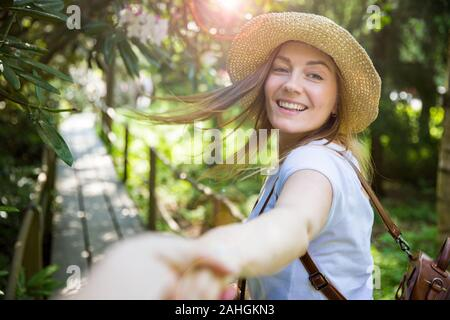Beautiful woman in straw hat travel in tropic forest, walking along wooden path, leading her partner. Tourist with backpack. Follow me concept. - Stock Photo