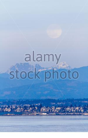 Full moon rising over the Cascade Mountains and Everett, Washington and Puget Sound - Stock Photo
