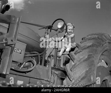 A girl sits on a tractor while eating ice cream, 1946 - Stock Photo