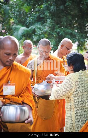 Phuket - Thailand, 7 May 2019 : Many Thai monk with alms bowl while old lady offering food put in the bowl, make hot smoke flow up in the morning time - Stock Photo
