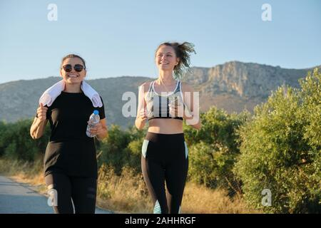 Two running women. Mother and daughter teenager running outdoor on road in mountains on summer sunny day. Family, healthy active sport lifestyle.