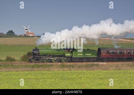 Steam locomotive Mayflower passing Weybourne windmill on the North Norfolk Railway - Stock Photo