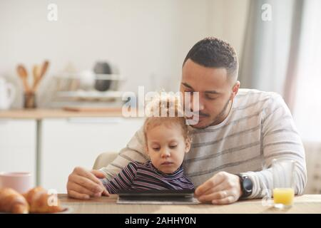 Warm-toned portrait of caring father with cute little girl using digital tablet together while sitting at wooden table in cozy kitchen, copy space